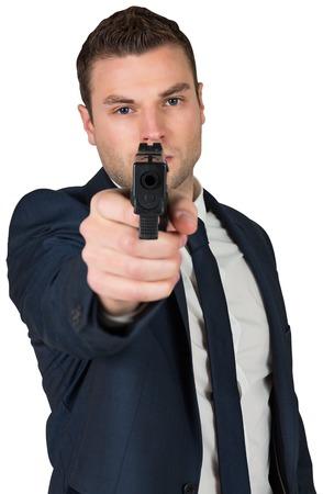 Serious businessman pointing a gun on white background photo