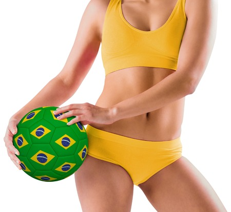 Fit girl in yellow bikini holding brazil football on white background photo