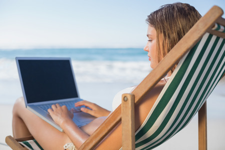 Smiling woman relaxing in deck chair on the beach using laptop on a sunny day photo