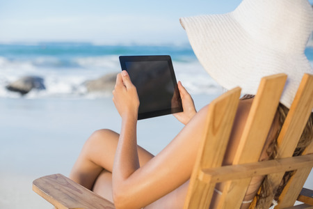Woman in straw hat relaxing in deck chair on the beach using tablet pc on a sunny day photo