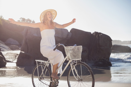 escapism: Beautiful blonde in white sundress on bike ride at the beach on a sunny day