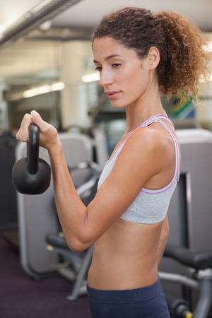 Fit woman lifting up kettlebell at the gym