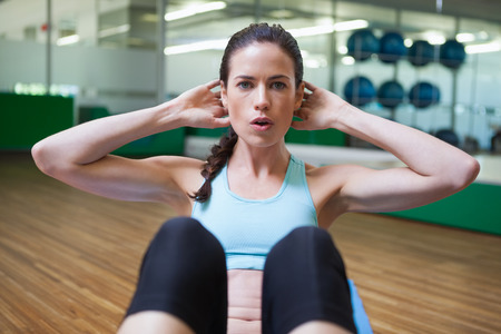 Fit brunette doing sit ups in fitness studio at the gym Stock Photo