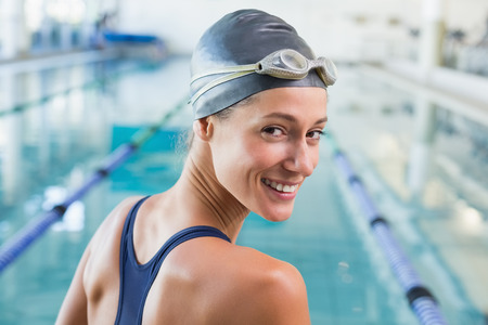 athletic woman: Pretty swimmer by the pool smiling at camera at the leisure center