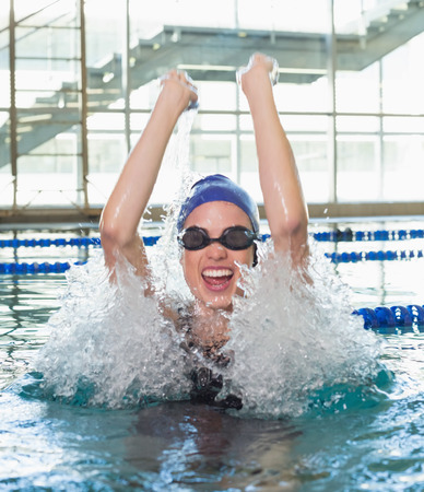 Excited swimmer cheering in the swimming pool at the leisure center Imagens