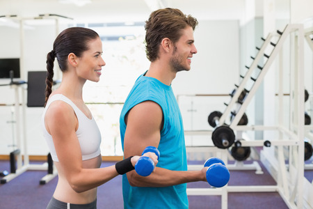 Fit couple exercising with blue dumbbells at the gym photo