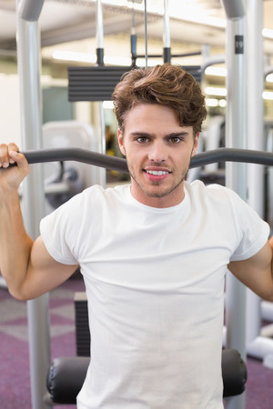 Fit man using weights machine for arms smiling at camera at the gym