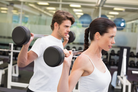 Fit couple lifting barbells together at the gym photo