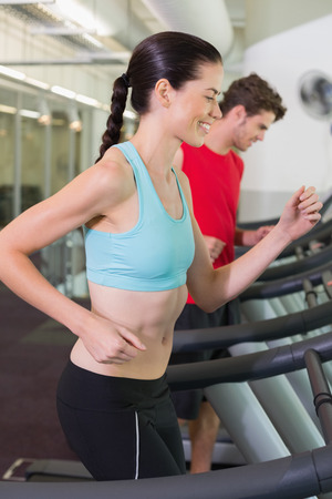 Fit happy couple running together on treadmills at the gym photo