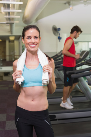 over shoulders: Smiling brunette with towel over shoulders at the gym Stock Photo