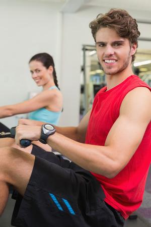 man working out: Hombre sonriente que se resuelve en la m�quina de remo en el gimnasio Foto de archivo