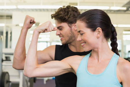 Fit attractive couple comparing biceps at the gym photo