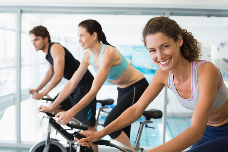 Fit people in a spin class with woman smiling at camera at the gym photo