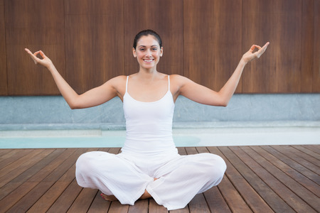 Peaceful happy woman in white sitting in lotus pose in health spa photo