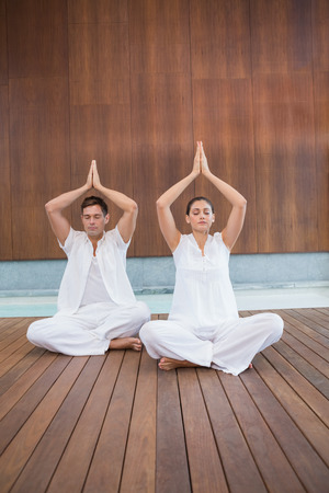 Attractive couple in white sitting in lotus pose with hands together in health spa photo