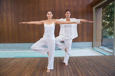 Peaceful couple in white doing yoga together in tree position in health spa photo
