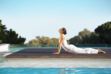Peaceful brunette in cobra pose poolside on a sunny day at the spa photo