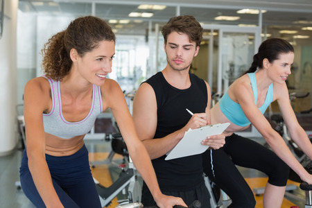 Fit women in a spin class with trainer taking notes at the gym photo
