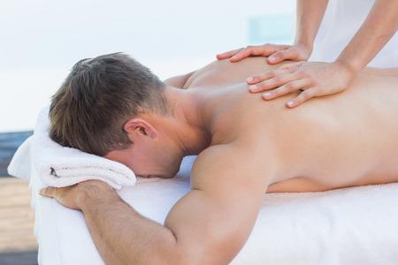 sin camisa: Hombre hermoso que consigue un masaje junto a la piscina al aire libre en el spa