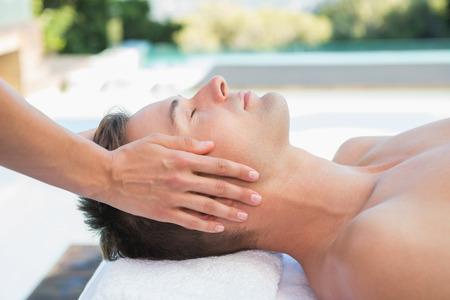 mannen en vrouwen: Rustige man krijgt een hoofdmassage aan het zwembad buiten in de spa Stockfoto