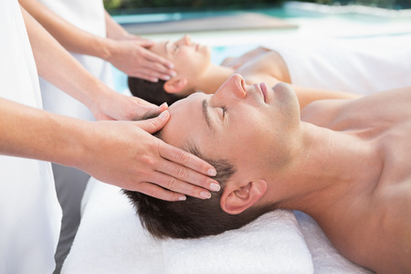 Content couple enjoying head massages poolside outside at the spa photo