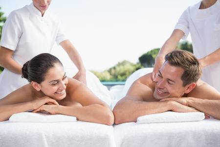 Smiling couple enjoying couples massage poolside outside at the spa