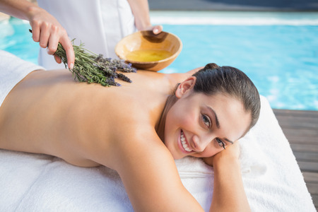 Smiling woman getting an aromatherapy treatment poolside outside at the spa photo