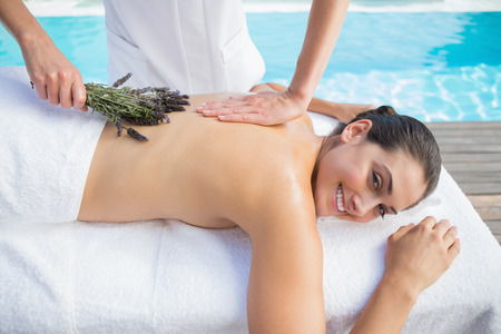 Smiling brunette getting an aromatherapy treatment poolside outside at the spa photo