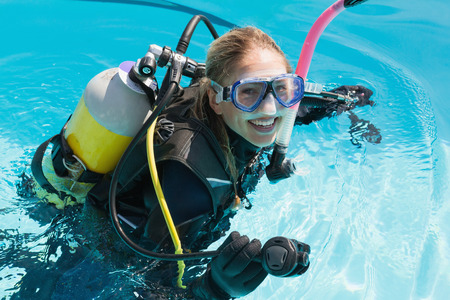 scuba woman: Smiling woman on scuba training in swimming pool on a sunny day Stock Photo
