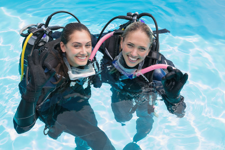 Smiling friends on scuba training in swimming pool making ok sign on a sunny day photo