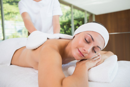 mitts: Beauty therapist rubbing smiling womans back with heated mitts in the health spa Stock Photo