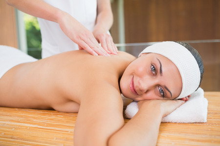 Smiling woman getting a back massage in the health spa