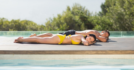 Gorgeous couple lying poolside on holidays on a sunny day photo