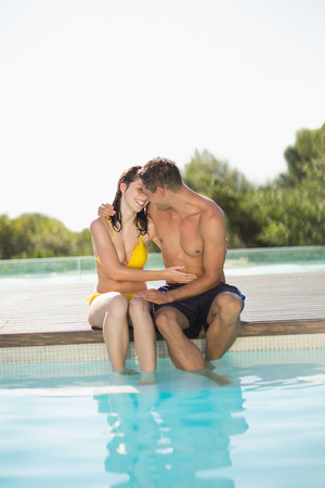 Gorgeous couple sitting poolside on holidays on a sunny day photo