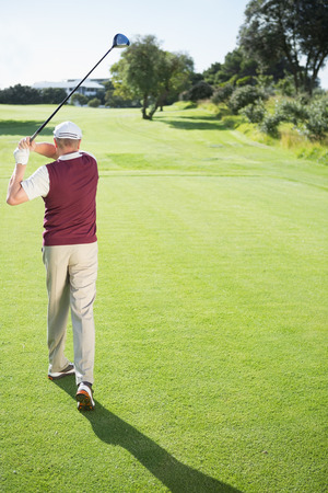 Golf player taking a shot on a sunny day at the golf course photo