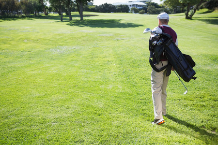 Golf player carrying his bag and walking on a sunny day at the golf course photo