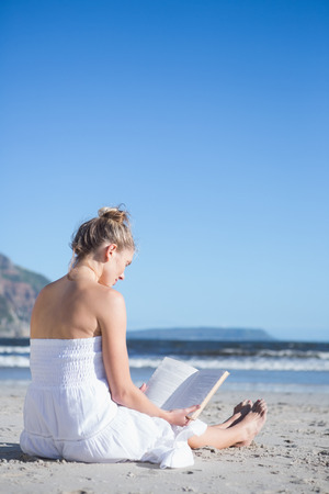 Content blonde in white dress sitting on the beach reading book on a bright day photo