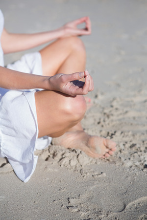 Woman in white dress meditating on the beach on a bright day photo
