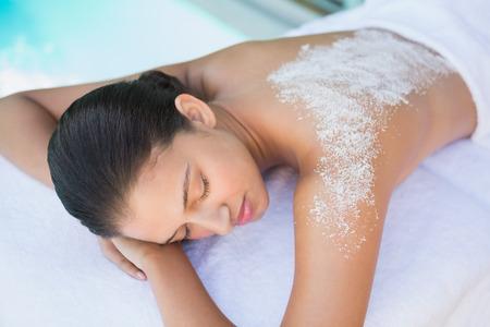 Calm brunette liggend op handdoek met zout behandeling op de rug buiten in de spa Stockfoto