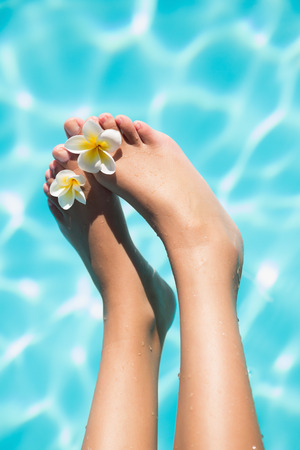 Feet dangling over swimming pool with flowers on a sunny day photo