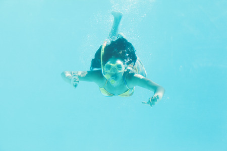 Brunette swimming underwater wearing snorkel on her holidays photo