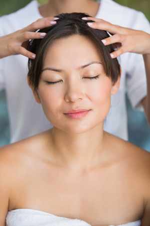 head massage: Relaxed brunette getting a head massage at the spa