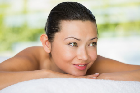 massage table: Smiling brunette lying on massage table at the spa
