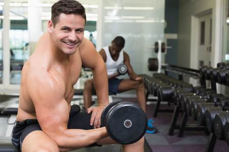 Handsome bodybuilder lifting heavy dumbbell smiling at camera at the gym photo