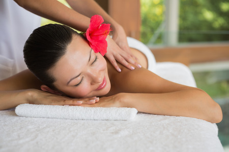 Brunette enjoying a peaceful massage at the health spa
