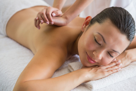 Brunette enjoying a peaceful massage with eyes closed at the\ health spa