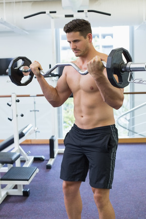 Shirtless focused bodybuilder lifting heavy barbell weight at the gym