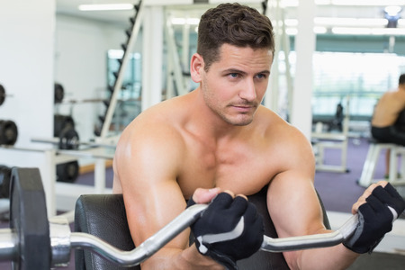 Shirtless focused bodybuilder lifting heavy barbell weight using bench at the gym photo
