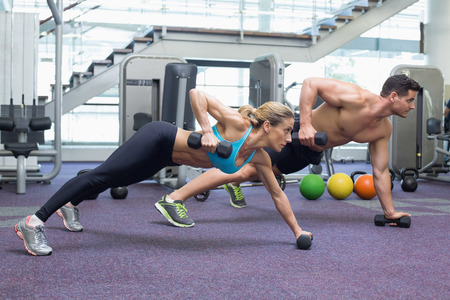 plank position: Bodybuilding man and woman holding dumbbells in plank position at the gym