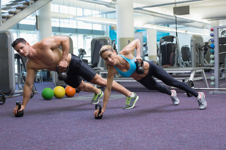 Bodybuilding man and woman lifting kettlebells in plank position at the gym photo